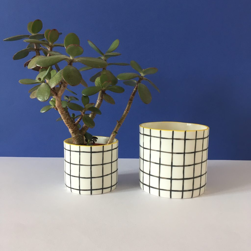 Two porcelain pots decorated with monochromatic grids, the left one is smaller and contains a plant