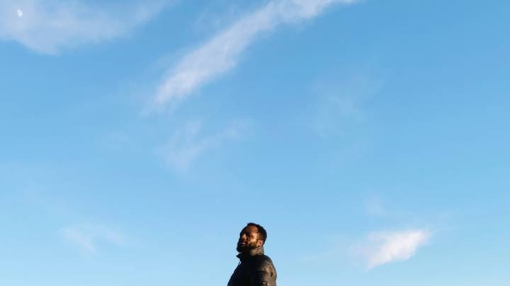 A picture of a man's head and shoulders with an enormous blue sky above and around him