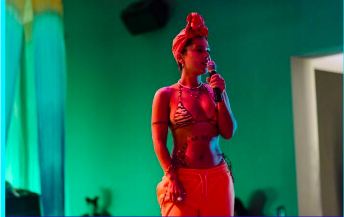 A black woman bathed in red light holding a microphone , the background behind them is green , they are wearing a headscarf, triangle bikini top and trousers