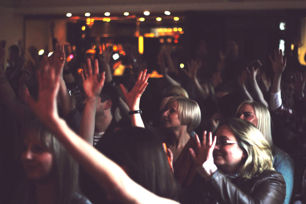 AN image of a crowd in a dark room - everyone is waving thier hands in the air - the image is slightly blurred showing the movement of bodies